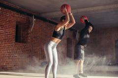 Hombre joven atlético y mujer en ropa de deportes que ejercitan con las bolas de medicina en gimnasio imagenes de archivo
