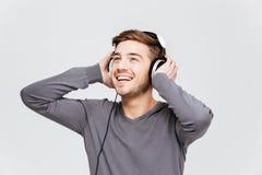 Hombre joven atractivo alegre en auriculares que escucha la música Imágenes de archivo libres de regalías
