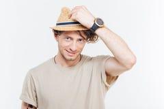 Hombre joven atractivo alegre en sombrero sobre el fondo blanco Imágenes de archivo libres de regalías
