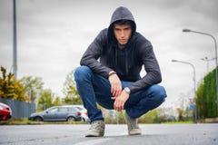 Hombre joven atractivo con sudadera con capucha y gorra de béisbol en calle de la ciudad Fotos de archivo libres de regalías