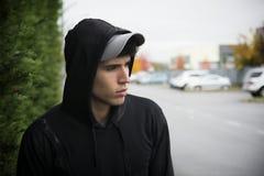 Hombre joven atractivo con sudadera con capucha y gorra de béisbol en ciudad fotos de archivo