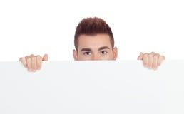 Hombre joven atractivo con un cartel en blanco Foto de archivo libre de regalías