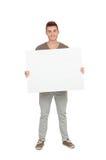 Hombre joven atractivo con un cartel en blanco Imagen de archivo libre de regalías