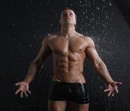 Hombre joven atractivo del músculo mojado que presenta bajo la lluvia Imagen de archivo libre de regalías