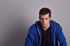 Hombre joven atractivo del pensador en sudadera con capucha azul Fotos de archivo libres de regalías