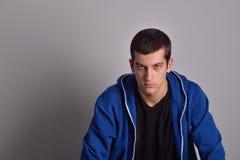 Hombre joven atractivo del pensador en sudadera con capucha azul Imagen de archivo libre de regalías