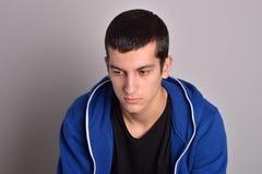 Hombre joven atractivo del pensador en una sudadera con capucha azul Fotos de archivo libres de regalías