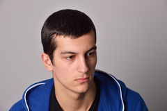 Hombre joven atractivo del pensador en una sudadera con capucha azul Imagen de archivo libre de regalías