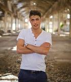 Hombre joven atractivo en almacén abandonado, vacío Imagen de archivo