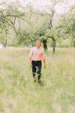 Hombre joven atractivo en camisa del melocotón que camina solamente a través de bosque de la primavera Imagenes de archivo