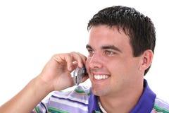 Hombre joven atractivo en el teléfono celular con sonrisa Fotos de archivo libres de regalías