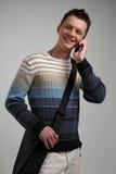Hombre joven atractivo en el teléfono celular, smilling. Foto de archivo