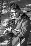 Hombre joven atractivo en la chaqueta roja que mira el reloj elegante a mano c Foto de archivo