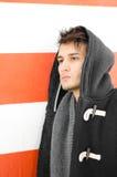 Hombre joven atractivo en sudadera con capucha contra la pared blanca y anaranjada Imagen de archivo