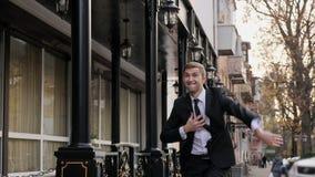 Hombre joven atractivo en un baile clásico del traje en la calle almacen de metraje de vídeo