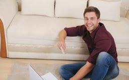 Hombre joven atractivo feliz que compra en línea por la tarjeta de crédito mientras que si Fotos de archivo libres de regalías