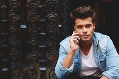 Hombre joven atractivo hermoso con una sonrisa dulce, hablando en el teléfono que se sienta en los pasos Imagen de archivo