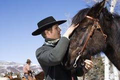 Hombre joven atractivo que acaricia el caballo Fotos de archivo libres de regalías