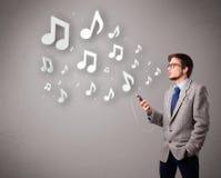 Hombre joven atractivo que canta y que escucha la música con musical Imágenes de archivo libres de regalías