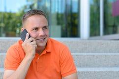 Hombre joven atractivo que charla en su móvil Fotografía de archivo libre de regalías