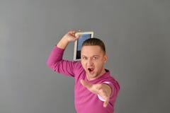 Hombre joven atractivo que coloca y que sostiene la avión-tabla Imagen de archivo libre de regalías