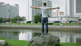 Hombre joven atractivo que defiende en una piedra grande el río almacen de video