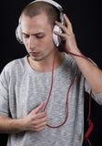 Hombre joven atractivo que escucha pensativamente la música en los auriculares Imágenes de archivo libres de regalías
