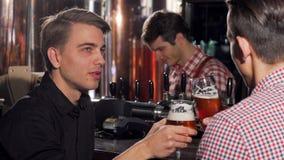 Hombre joven atractivo que goza bebiendo la cerveza con su amigo almacen de metraje de vídeo