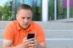 Hombre joven atractivo que manda un SMS en su móvil Imagenes de archivo