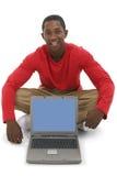 Hombre joven atractivo que señala a la pantalla de la computadora portátil fotografía de archivo