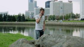 Hombre joven atractivo que se coloca cerca de una piedra grande y que habla en el teléfono móvil almacen de metraje de vídeo