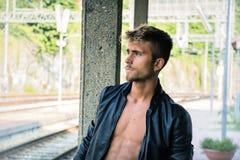 Hombre joven atractivo que se coloca en pistas de ferrocarril fotos de archivo libres de regalías