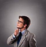 Hombre joven atractivo que se coloca y que piensa con el espacio de la copia Fotos de archivo