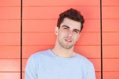 Hombre joven atractivo que se inclina contra la pared anaranjada Foto de archivo libre de regalías