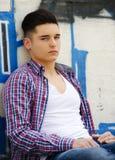 Hombre joven atractivo que se sienta contra pintada colorida imagen de archivo libre de regalías