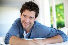 Hombre joven atractivo que se sienta en el sofá Fotos de archivo