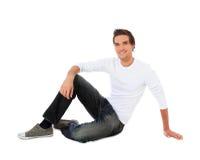 Hombre joven atractivo que se sienta en el suelo Imagen de archivo libre de regalías