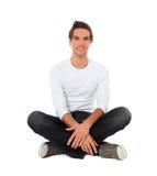 Hombre joven atractivo que se sienta en el suelo Fotografía de archivo libre de regalías
