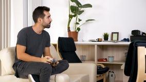 Hombre joven atractivo que se sienta en su sofá y que juega a los videojuegos fotos de archivo