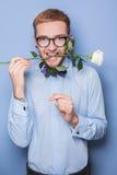 Hombre joven atractivo que sonríe con una rosa blanca en su boca Fecha, cumpleaños, tarjeta del día de San Valentín Foto de archivo libre de regalías
