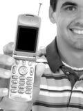 Hombre joven atractivo que sostiene hacia fuera el teléfono celular en blanco y negro imágenes de archivo libres de regalías