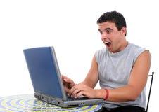 Hombre joven atractivo que trabaja en la computadora portátil con S Imagen de archivo libre de regalías