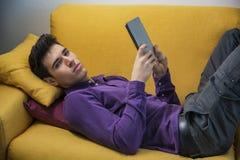 Hombre joven atractivo que usa la tableta mientras que pone Foto de archivo