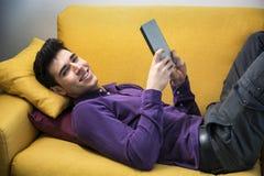 Hombre joven atractivo que usa la tableta mientras que pone Fotografía de archivo