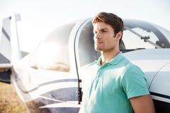 Hombre joven atractivo serio cerca del pequeño aeroplano fotografía de archivo
