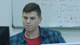 Hombre joven atractivo usando el ordenador en su lugar de trabajo Concentran al oficinista que hace su trabajo metrajes