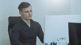 Hombre joven atractivo usando el ordenador en su lugar de trabajo Oficinista que sonr?e y que mira la c?mara almacen de video