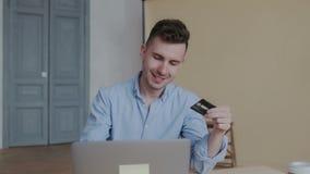 Hombre joven atractivo y feliz apuesto en camisa azul usando el ordenador portátil para hacer compras en línea con la tarjeta de  almacen de metraje de vídeo