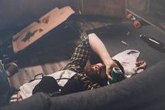 Hombre joven barbudo borracho que duerme en el sofá con el sujetador y la lata de cerveza Imagen de archivo
