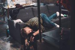 Hombre joven barbudo borracho que sostiene la botella de cerveza que miente en el sofá en sitio sucio Fotos de archivo